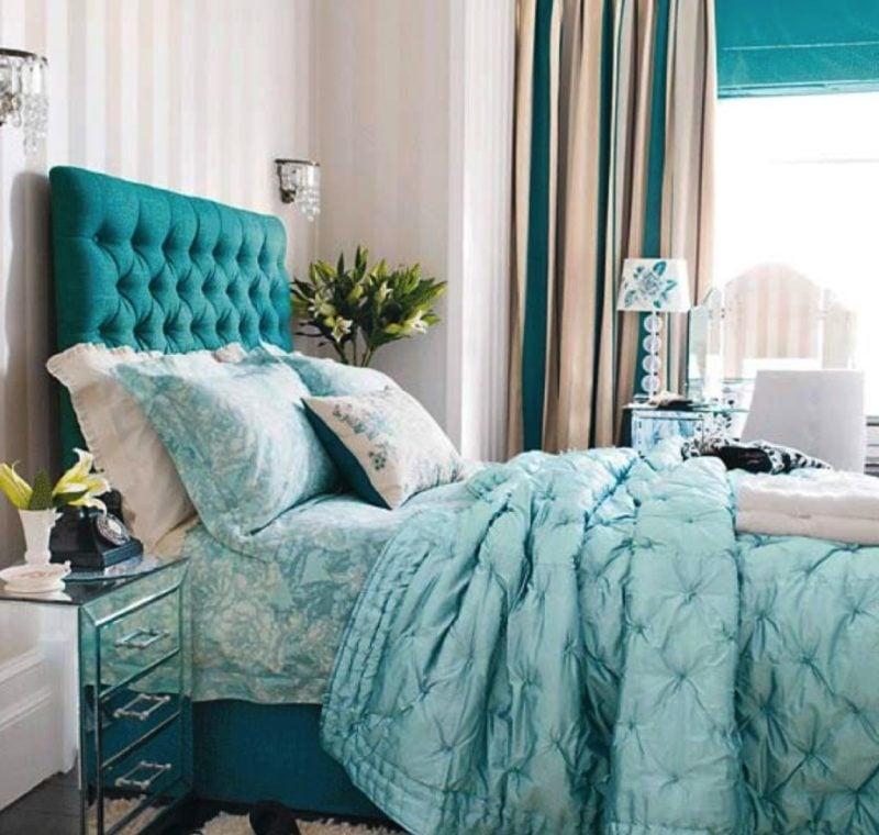 Quarto planejado com decoração luxuosa e cabeceira estofada azul.
