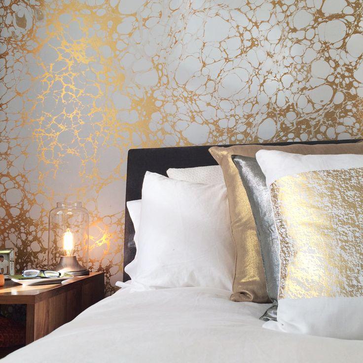 Quarto luxuoso com papel de parede dourado.