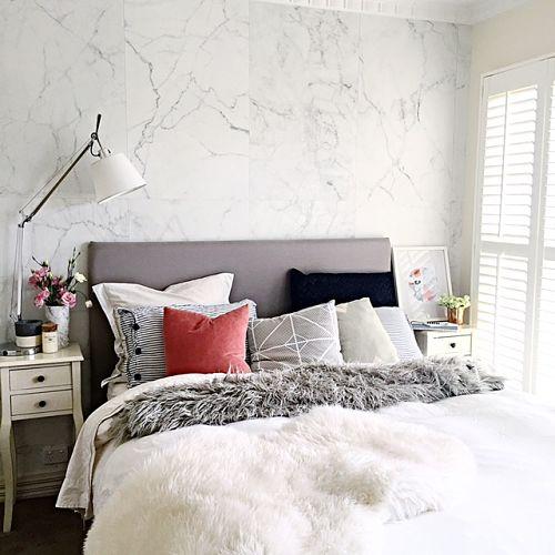 Quarto de casal com papel de parede com estampa de mármore.