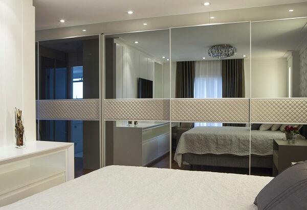 Quarto luxuoso com armário espelhado e detalhe estofado.