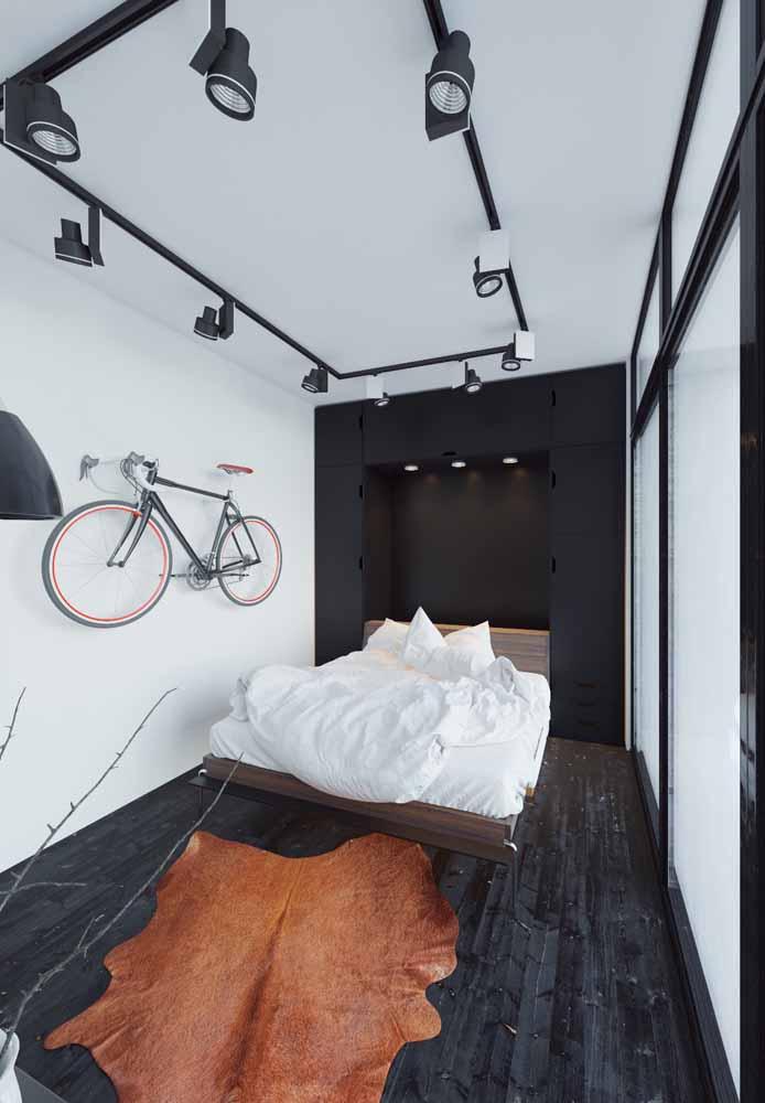 Quarto moderno com armário preto e trilho de luz.