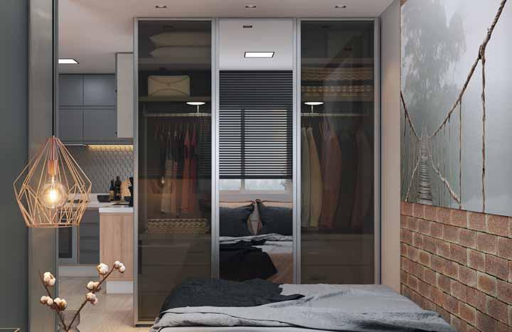 Quarto moderno com pendente suspenso e guarda-roupa com porta de vidro.