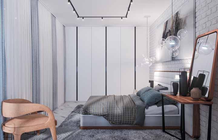 Quarto moderno com trilho de luz e parede de tijolinho branco.