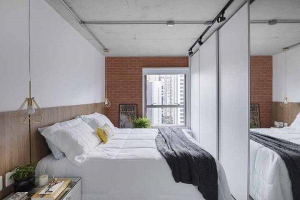 Quarto pequeno moderno com parede de tijolinho e pendente suspenso.