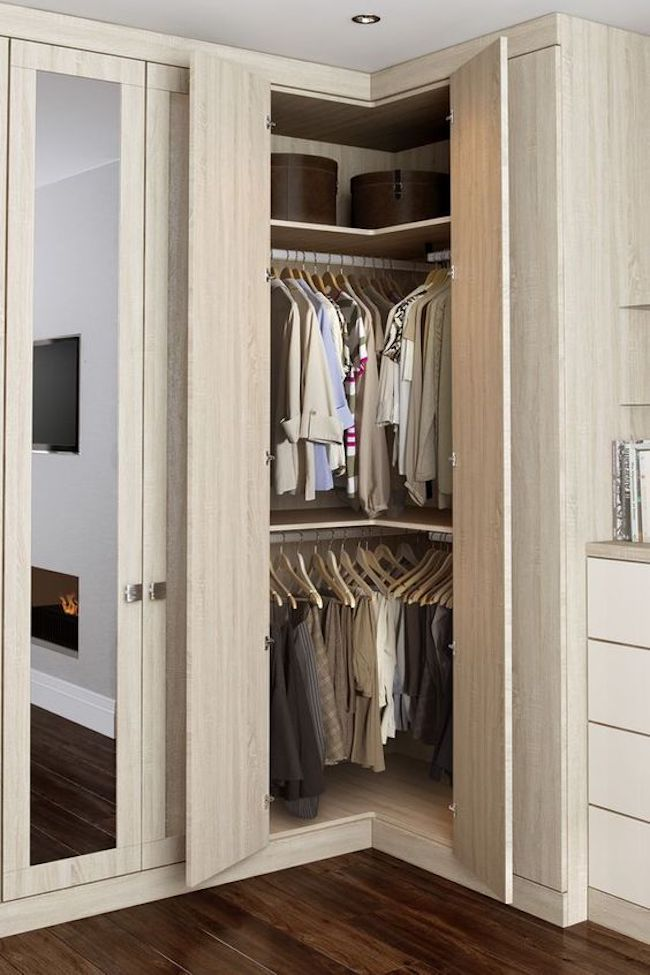 Guarda-roupa planejado de canto com acabamento de madeira.
