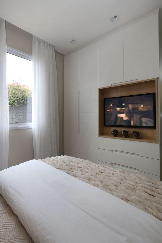 Guarda-roupa planejado com TV embutida e decoração simples.