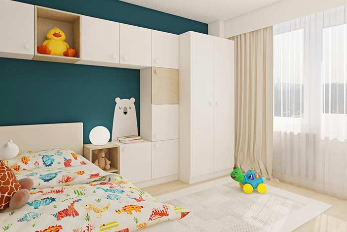 Quarto infantil decorado com parede azul e armário branco.