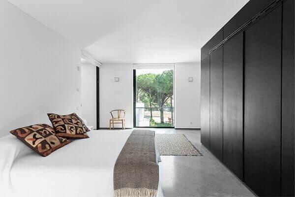 Quarto moderno com decoração minimalista e armário preto.
