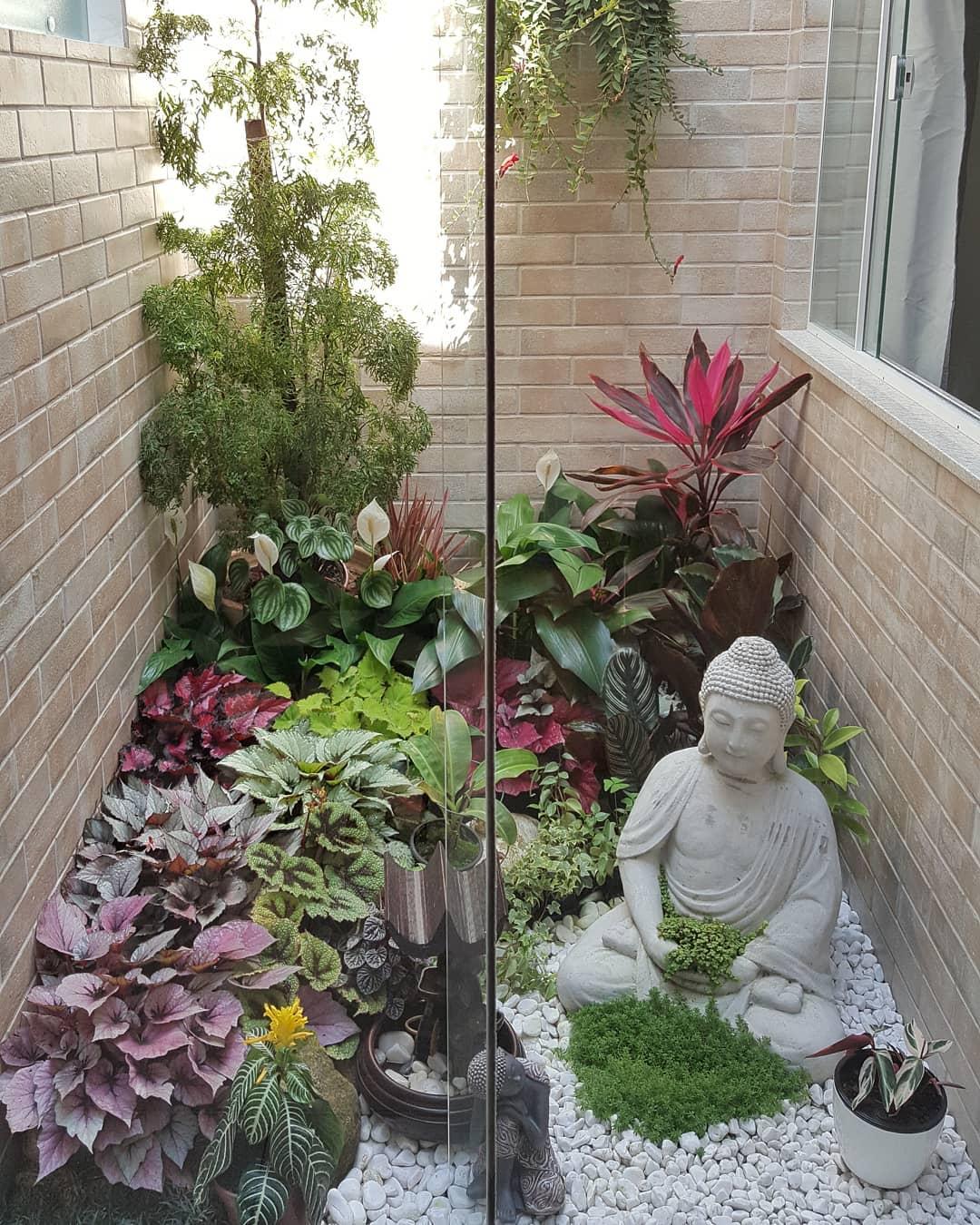 Jardim de inverno com escultura e fonte.