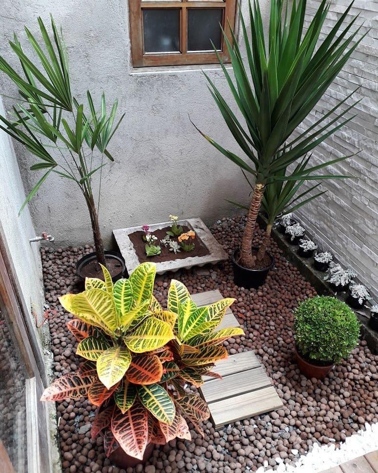Jardim de inverno com seixo rolado e vasos de planta.