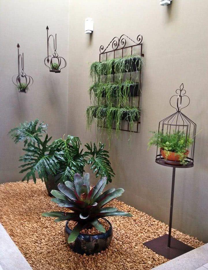 Jardim de inverno com vasos verticais e bromélias.