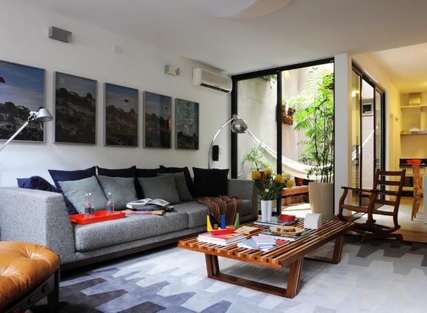 Decoração de dala de estar simples com mesa de centro de madeira e sofá cinza.