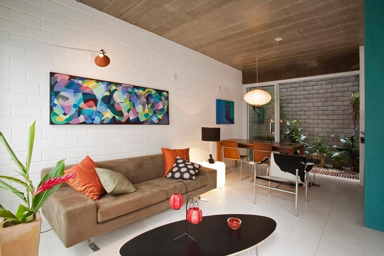 Sala com decoração moderna, vasos de planta, parede com revestimento de tijolinho branco e cadeira de couro.