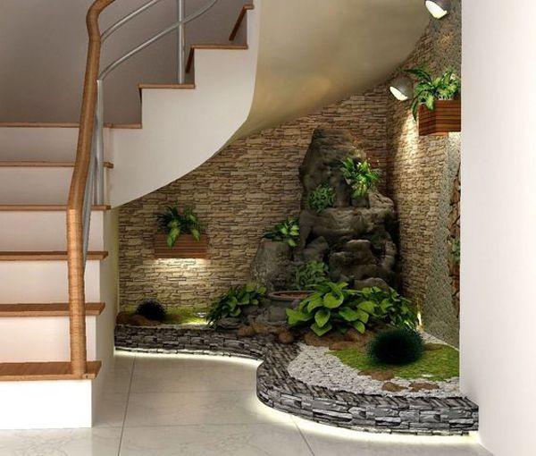 Jardim de inverno embaixo da escada com fonte e iluminação.