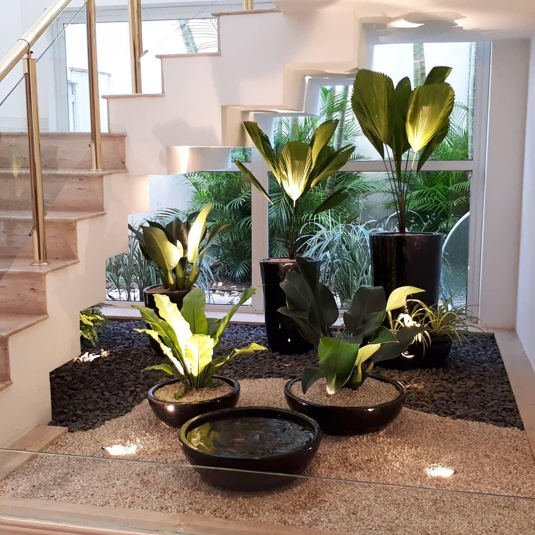Jardim de inverno embaixo da escada com vasos de planta e fonte de água.