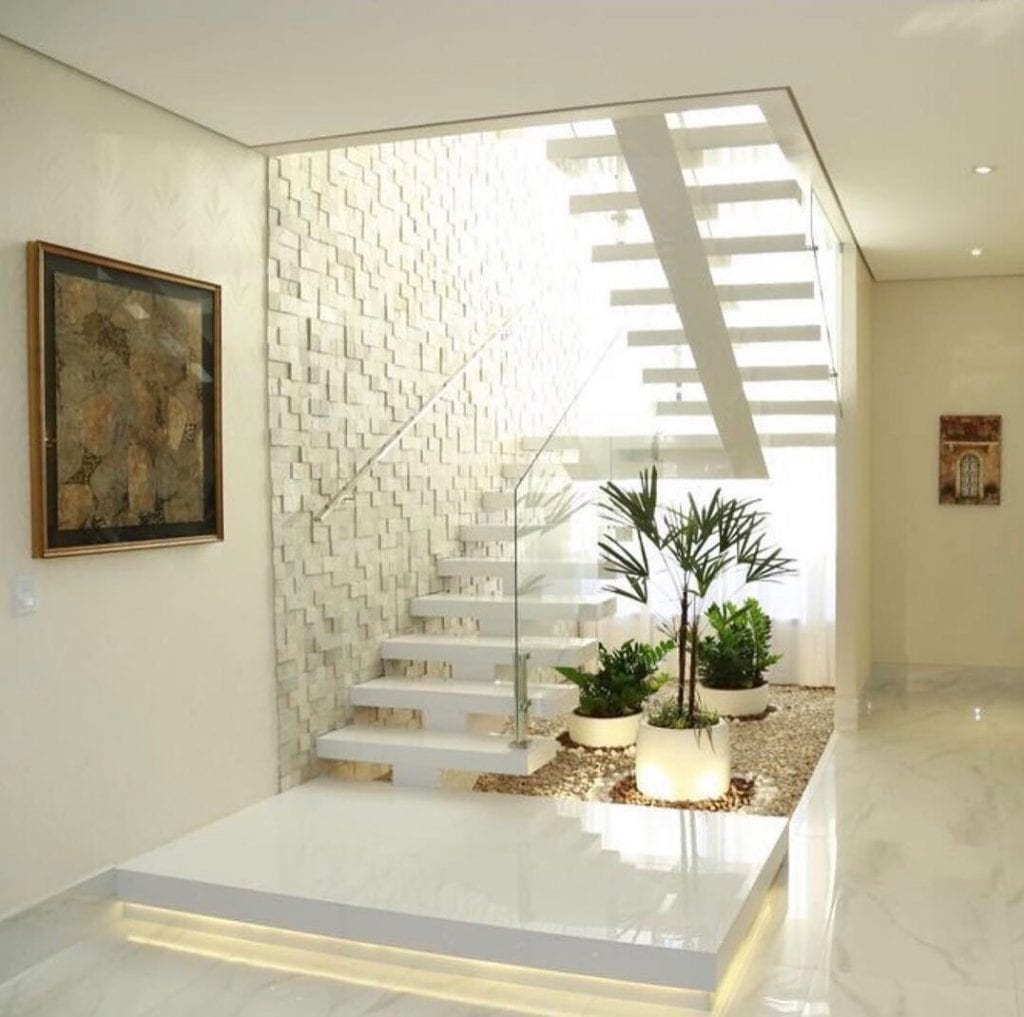 Jardim de inverno pequeno embaixo da escada branca.