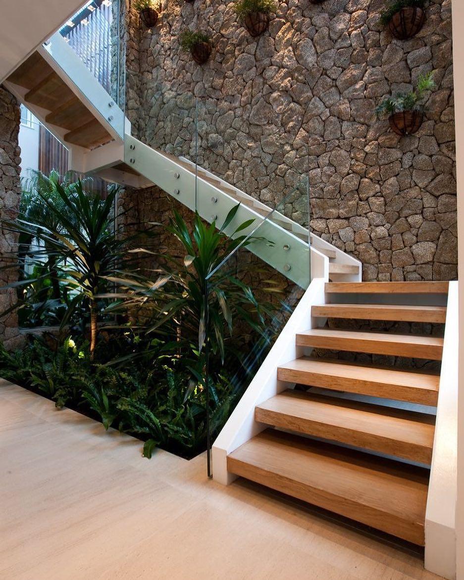 Jardim de inverno embaixo da escada com palmeiras e bromélias.