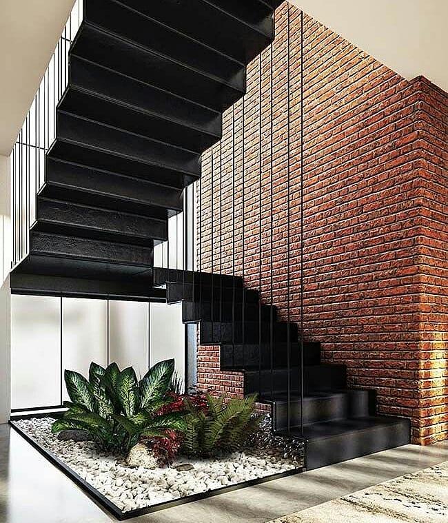 Jardim de inverno embaixo da escada moderna preta e seixo branco.