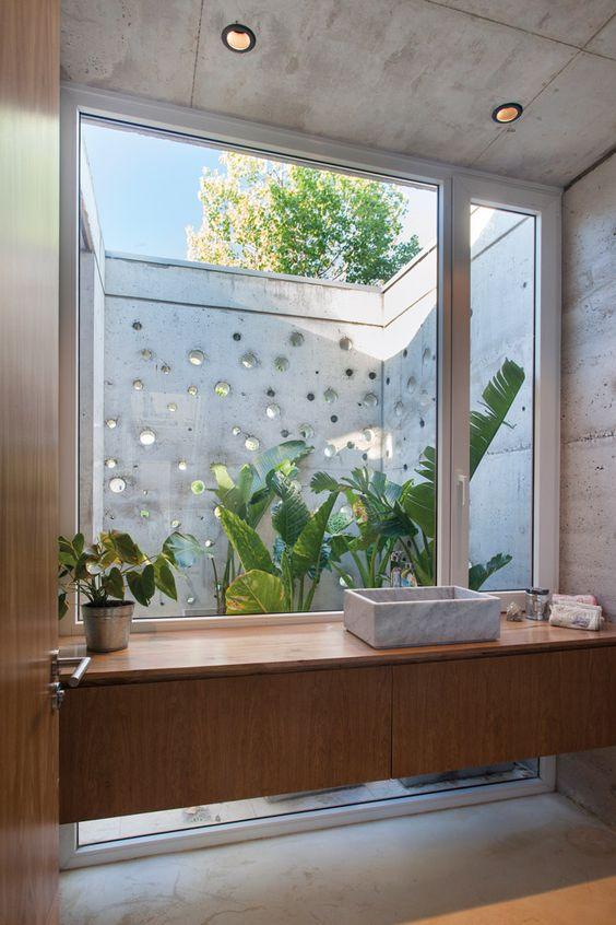 Banheiro moderno com bancada de madeira e cuba de mármore.