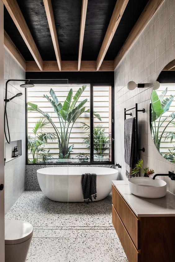 Banheiro luxuoso com banheira oval e armário de madeira.