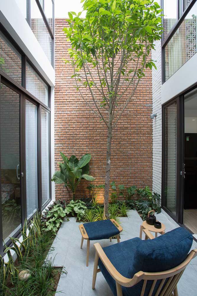 Casa com jardim de inverno com parede de tijolinho aparente.