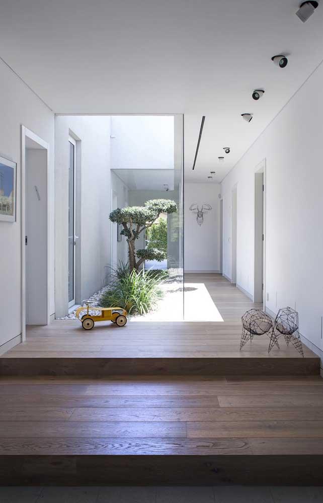 Casa com jardim de inverno com árvore e seixo rolado.