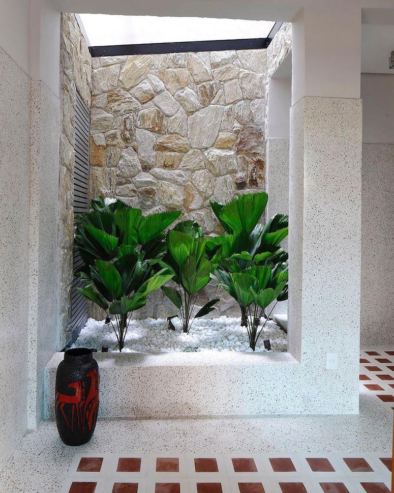 Jardim de inverno pequeno com revestimento de pedra e seixo branco.