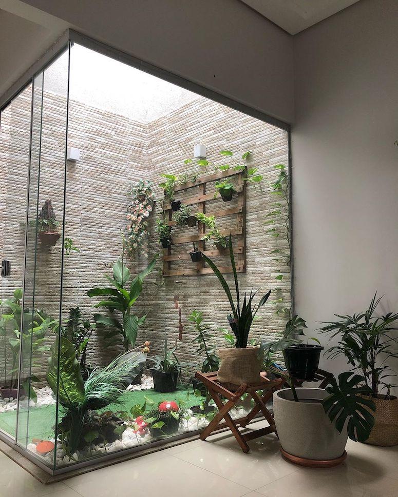 Jardim de inverno pequeno com parede de vidro.