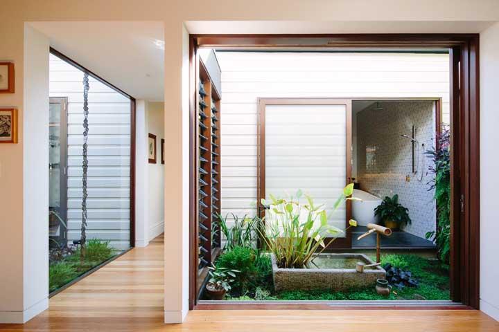 Casa com jardim de inverno com fonte e madeira.