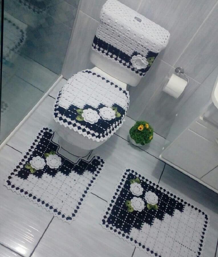 Jogo de banheiro de crochê branco e azul.
