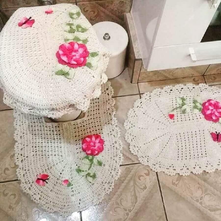 Jogo de banheiro de crochê branco com flores rosas.