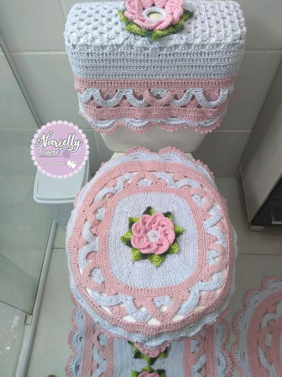 Jogo de banheiro de crochê branco e rosa com flores.
