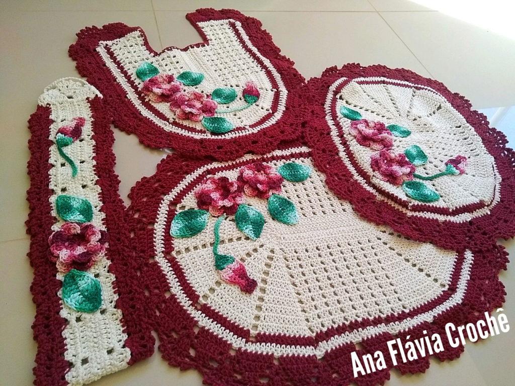 Jogo de banheiro de crochê branco e roxo com flores.
