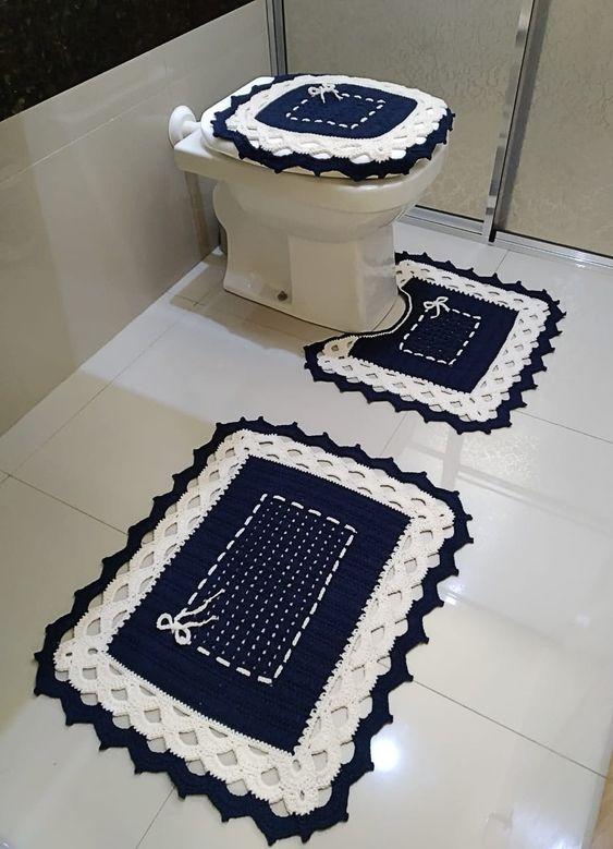 Vaso sanitário com capa e tapete bordado azul e branco.