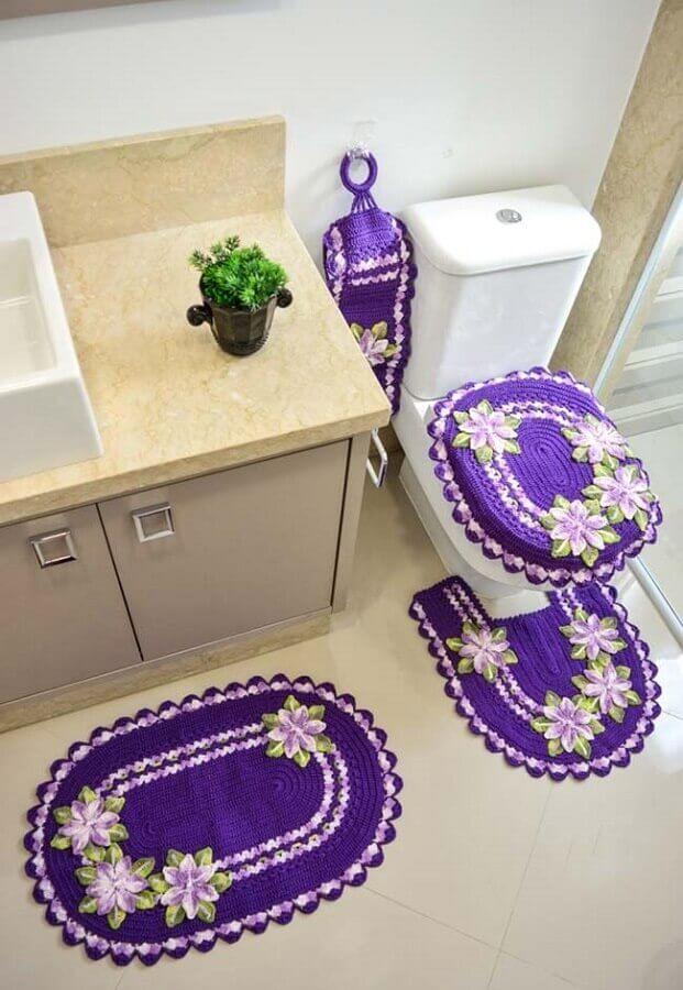 Jogo de banheiro de crochê roxo com flores.