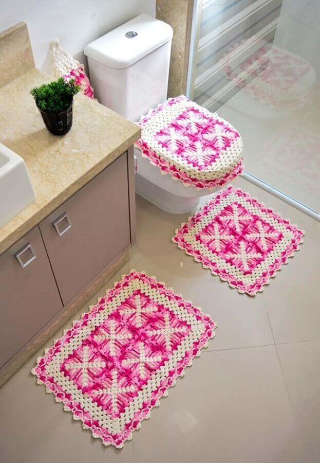Vaso sanitário com capa e tapete quadrado rosa.