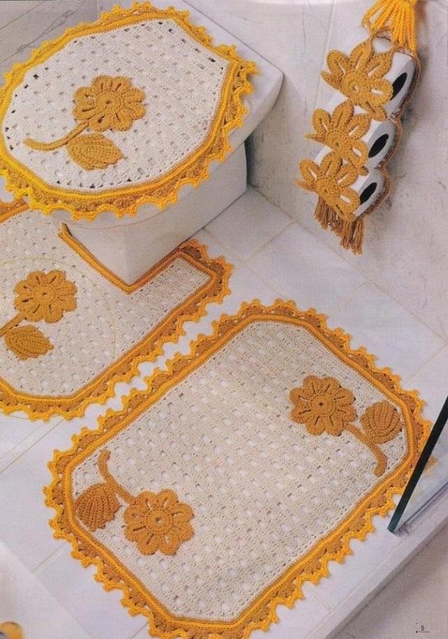 Vaso sanitário com capa e tapete bordado branco e amarelo.