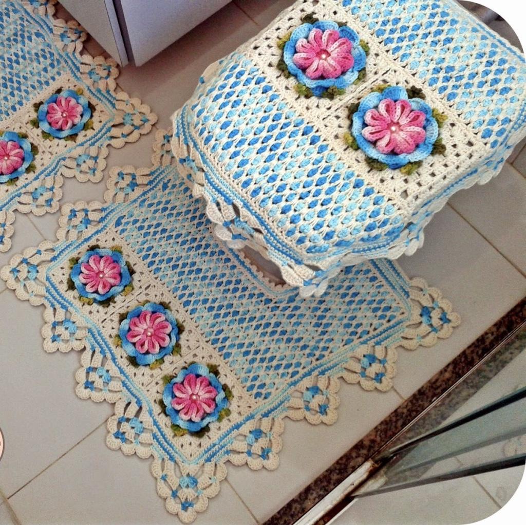 Jogo de banheiro de crochê branco e azul com flores.