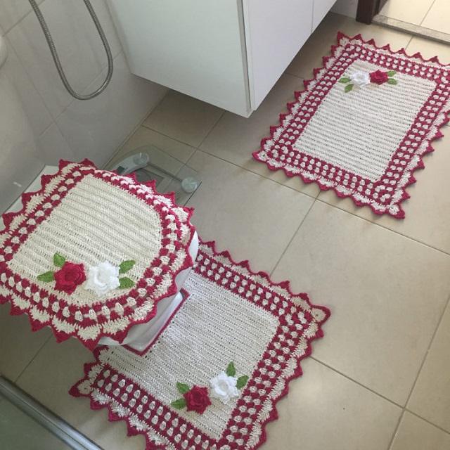 Jogo de banheiro de crochê branco e vermelho com flores.