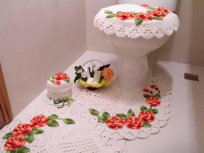 Vaso sanitário decorado com capa e tapete bordado com flores.