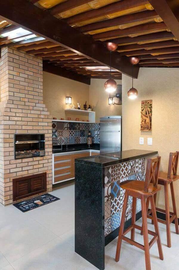 Modelo de churrasqueiras de alvenaria com bancada de granito e azulejo decorado.