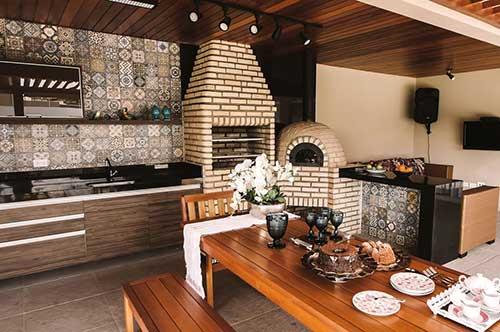 Modelo de churrasqueira de alvenaria e decoração rústica com azulejo decorado.