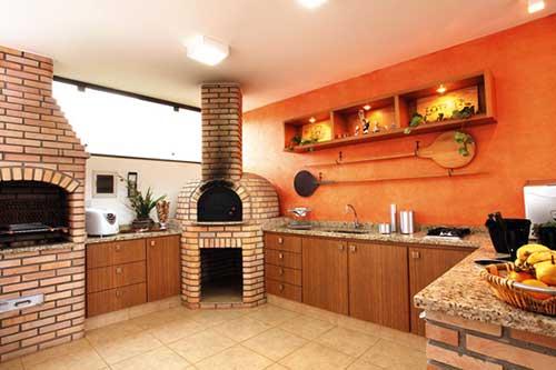 Modelo de churrasqueira de alvenaria com decoração rústica e laranja.
