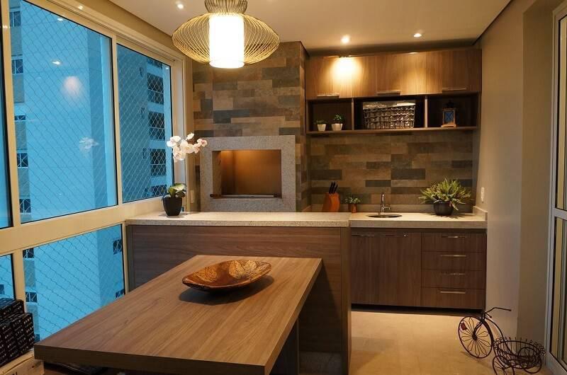 Varanda gourmet com acabamento de madeira e lustre moderno.