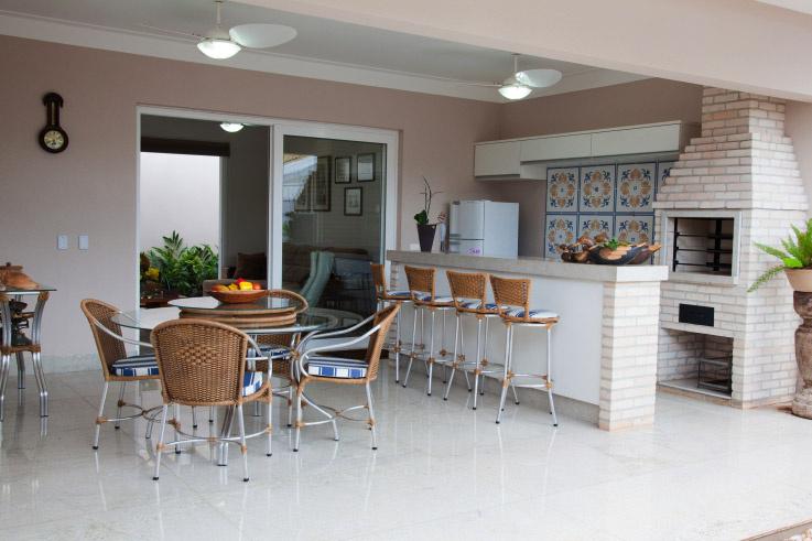 Varanda decorada com cadeiras de vinil, mesa de vidro e azulejo decorado.
