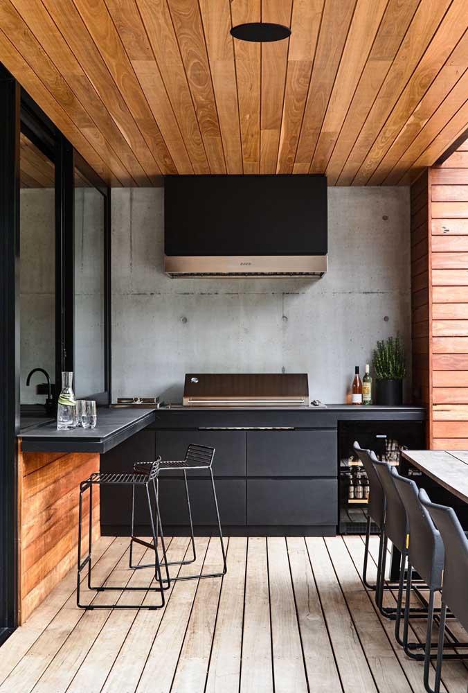 Varanda gourmet moderna com armários pretos e piso de madeira.