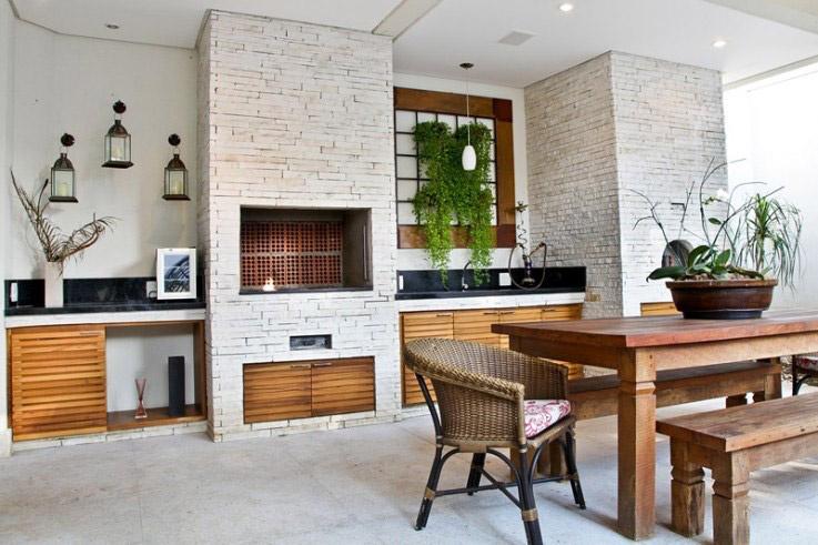 Varanda rústica com tijolinho branco e mesa de madeira.