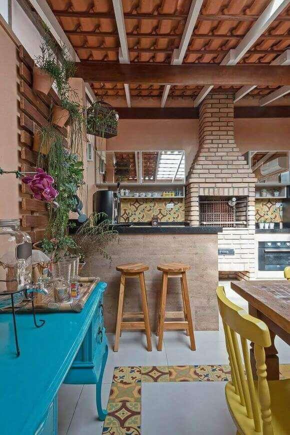Varanda gourmet com decoração colorida e rústica.