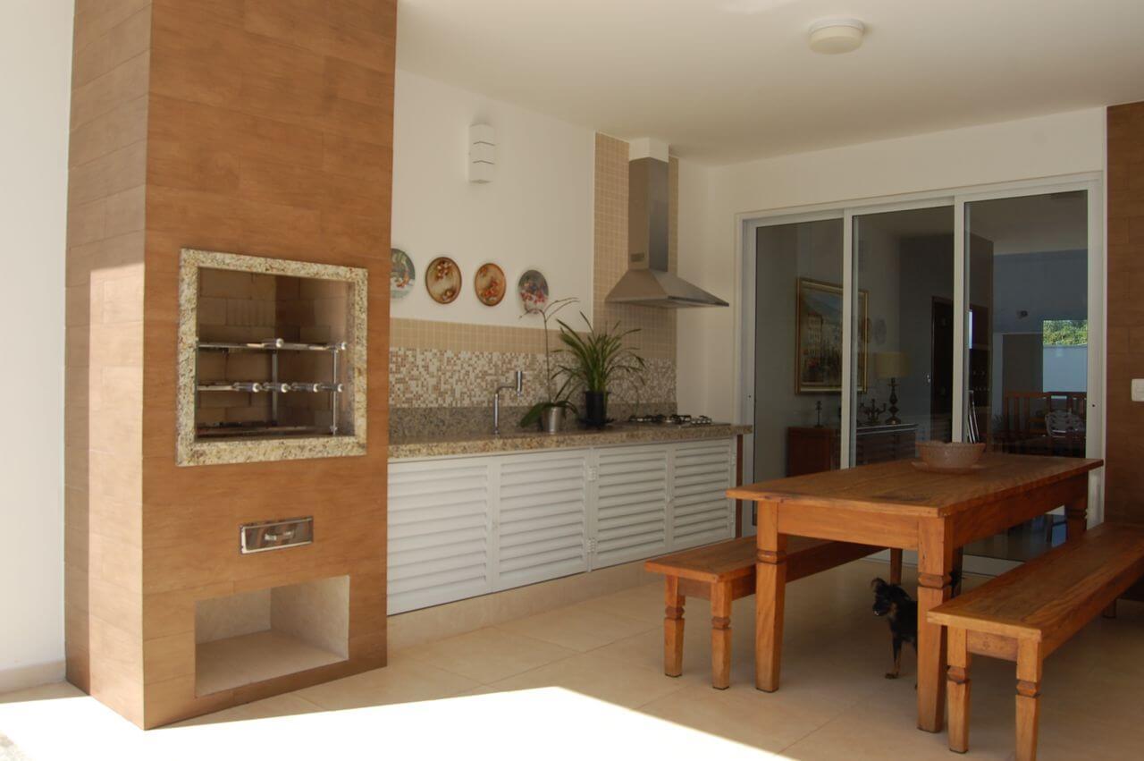 Varanda gourmet grande e simples com mesa de madeira.