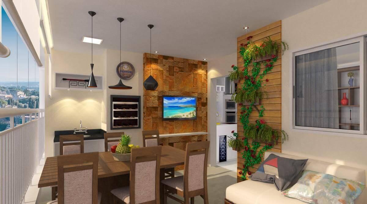Varanda gourmet com televisão, mesa e cozinha.